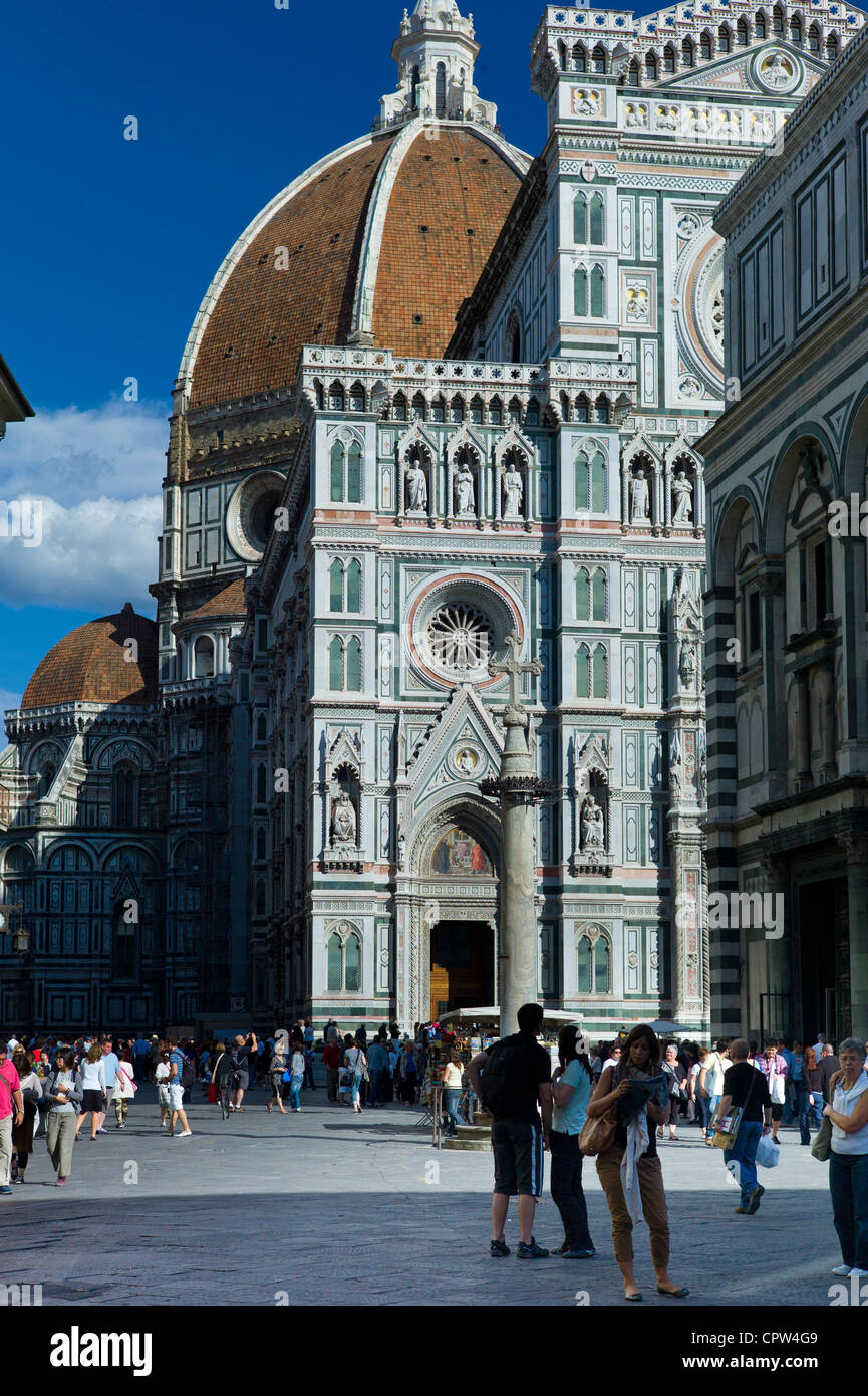 Tourists by Il Duomo di Firenze, Cathedral of Florence, and the Baptistry in Piazza di San Giovanni, Tuscany, Italy - Stock Image