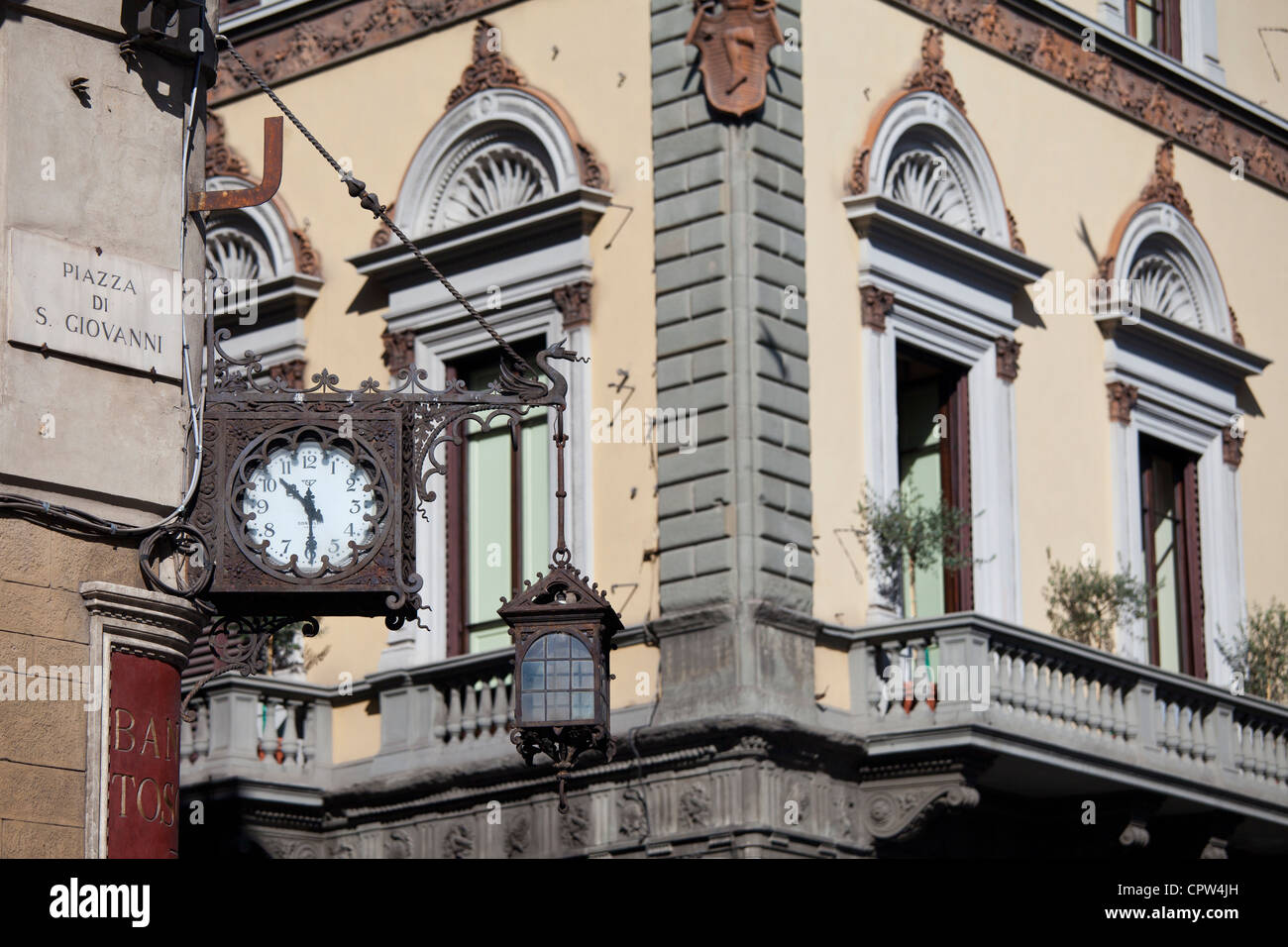 Ancient clock with Roman numerals on Banca Toscana in Piazza di San Giovanni and via de Martelli in Florence, Tuscany, - Stock Image