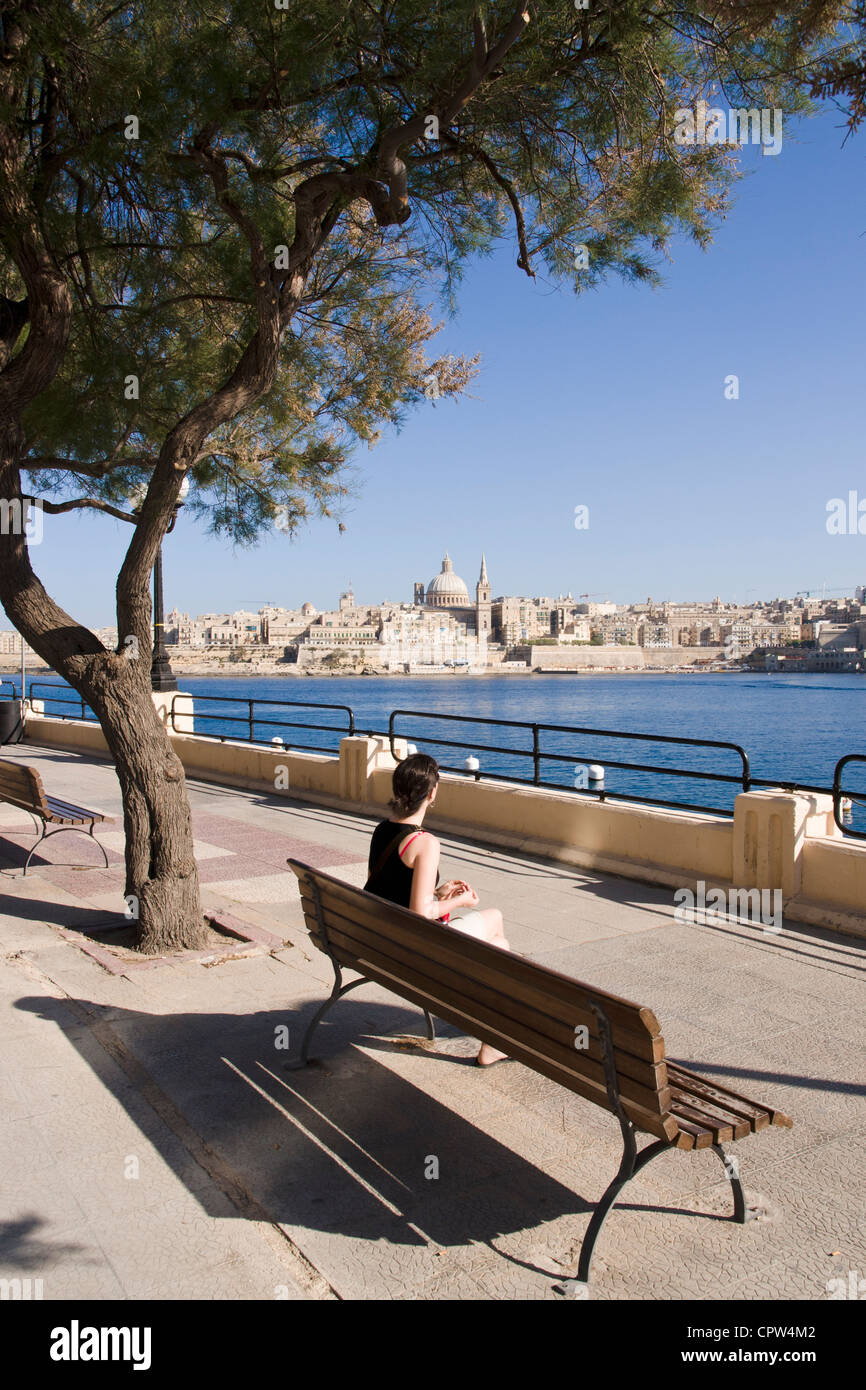 Young woman on a bench enjoying the view on Valletta from Sliema waterfront, Malta. - Stock Image