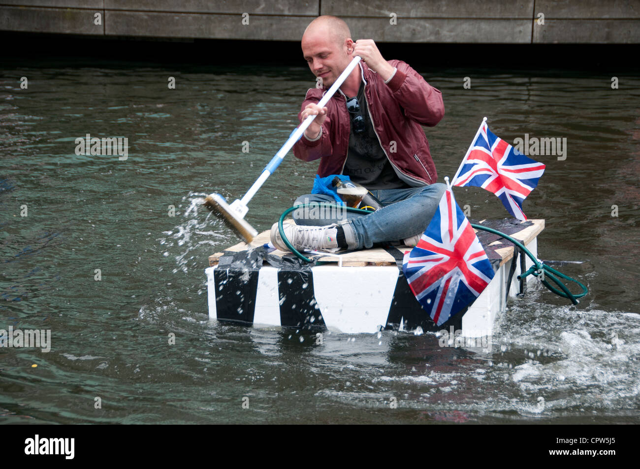 Queen's Jubillegal flotilla floating party, Regent's Canal. Man on home-made raft paddling with floor mop - Stock Image