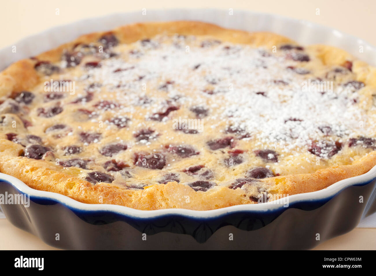 Famous French dessert, cherry clafoutis, with asprinkle of icing sugar. Absolutely delicious! Shallow DOF, focus - Stock Image