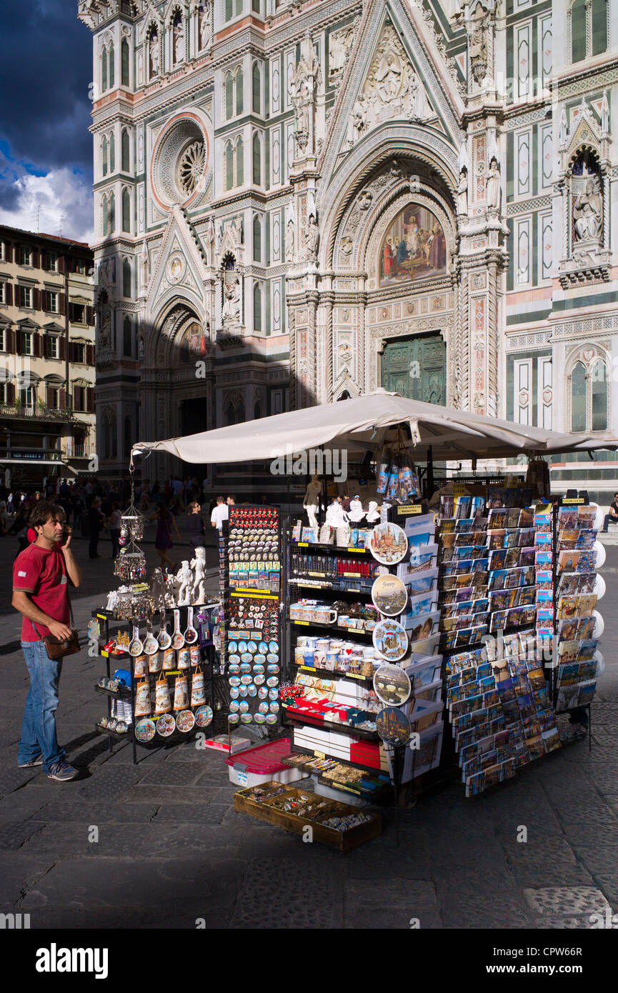 Man using cellphone by souvenir stall selling guidebooks, maps and souvenirs in Piazza di San Giovanni, Tuscany, - Stock Image