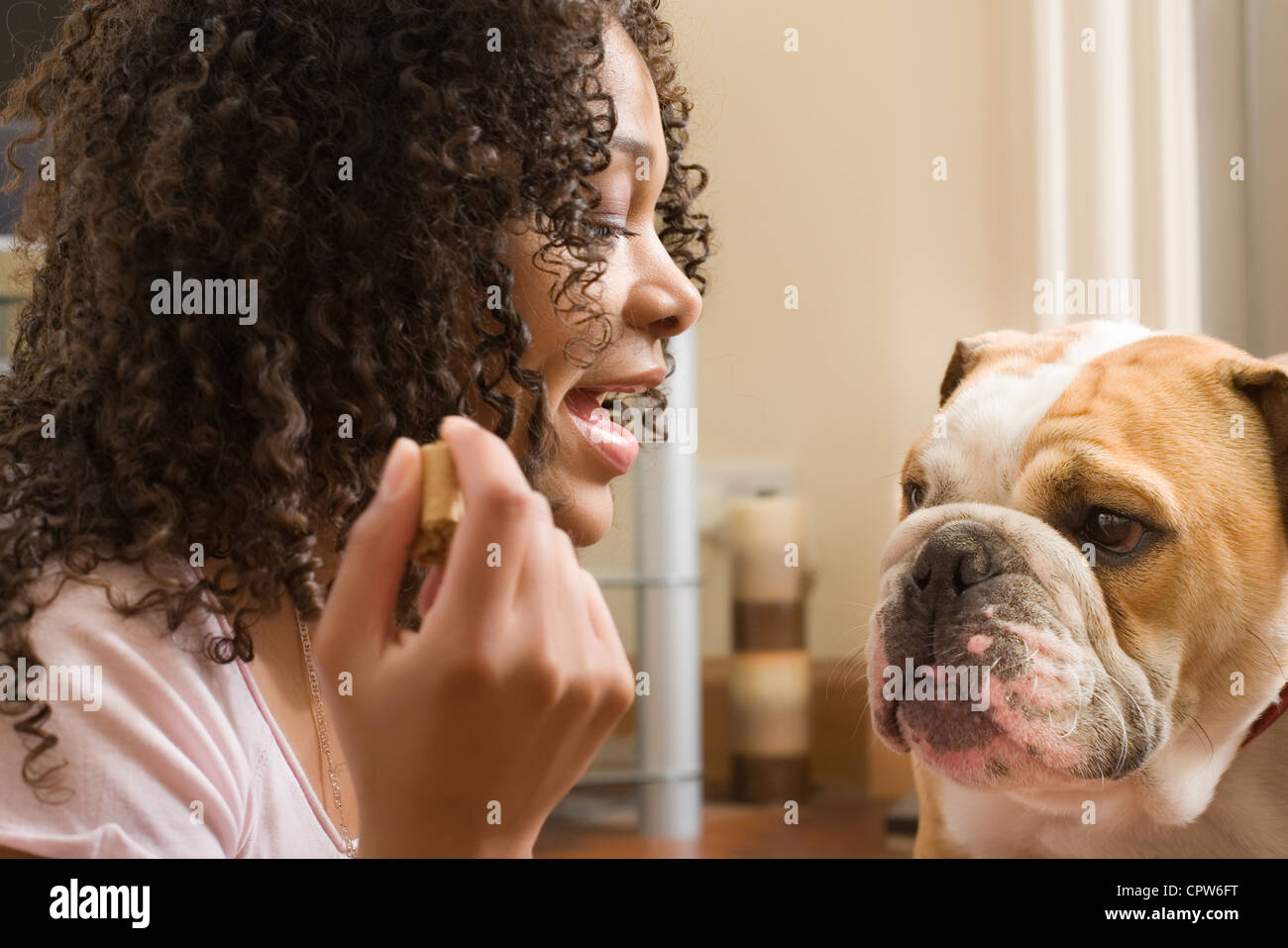 Young woman with treat in-hand speaking to her puppy dog - Stock Image