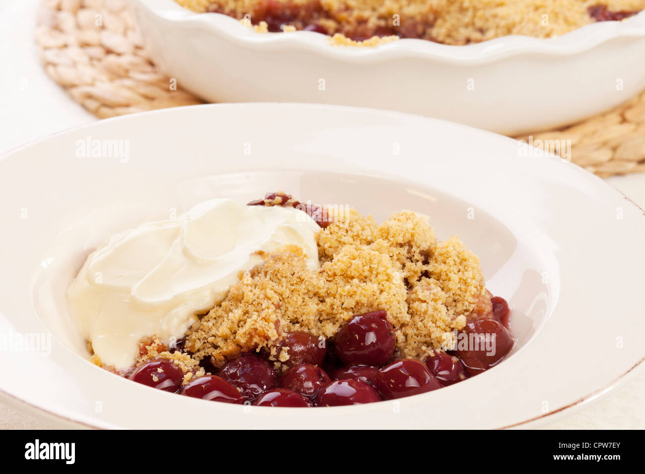 A bowl of cherry crumble served with greek yoghurt. - Stock Image