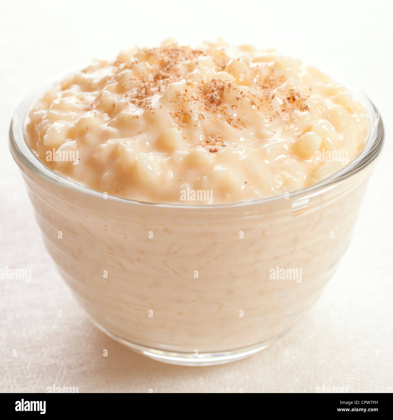 Rice pudding sprinkled with nutmeg in an individual glass bowl. - Stock Image