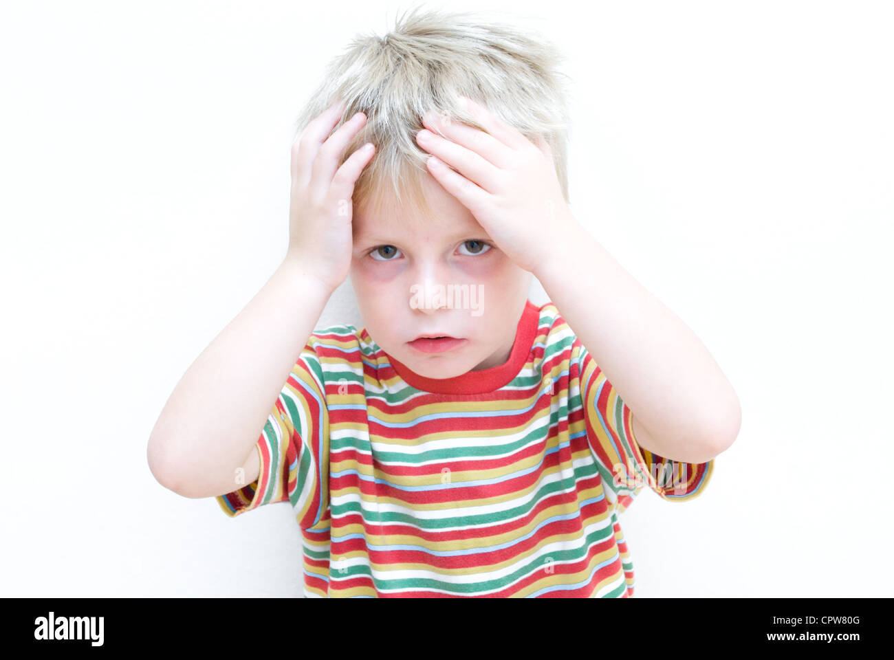 Upset child holding his head in his hands. - Stock Image