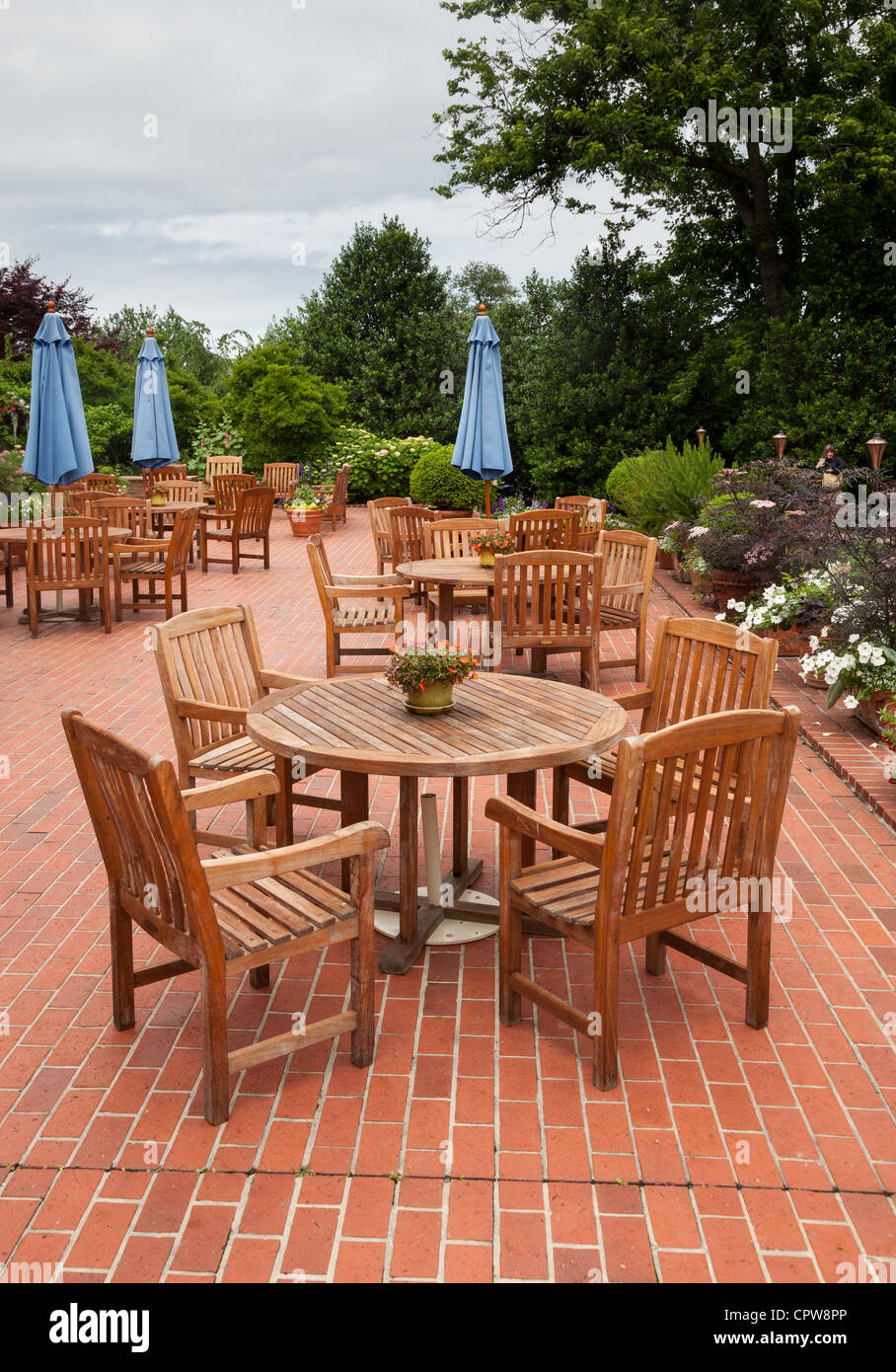 Tables and chairs on brick patio in bar cafe or restaurant - Stock Image
