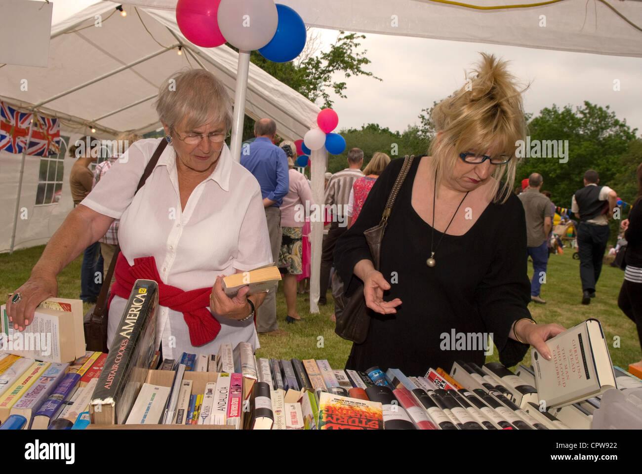 Women perusing book stall at Dockenfield fete & Diamond Jubilee celebration day, Dockenfield, Surrey, UK. - Stock Image