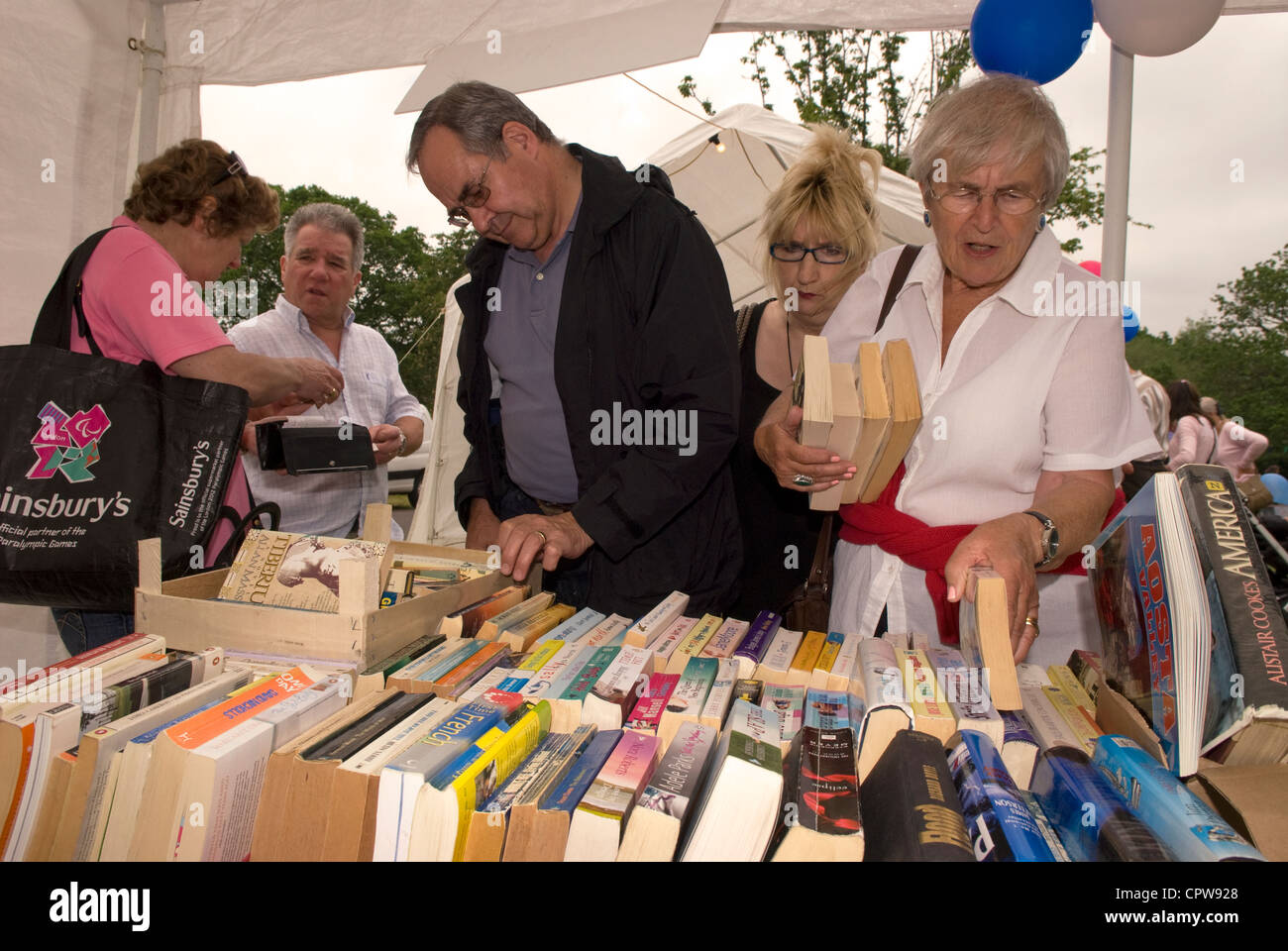 People perusing book stall at Dockenfield fete & Diamond Jubilee celebration day, Dockenfield, Surrey, UK. - Stock Image