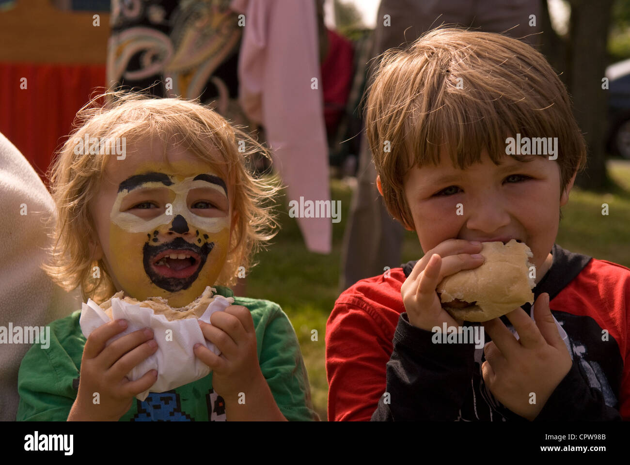 Two young boys eating burgers at Dockenfield fete & Diamond Jubilee celebration day, Dockenfield, Surrey, UK. - Stock Image