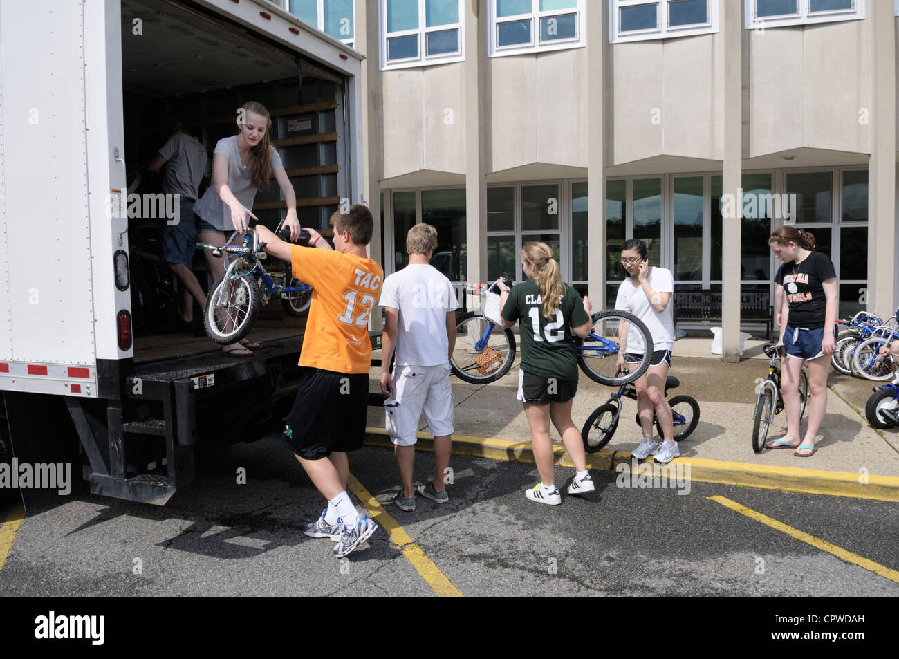 High school student volunteers doing community service loading donated used bikes onto truck to distribute to poor - Stock Image