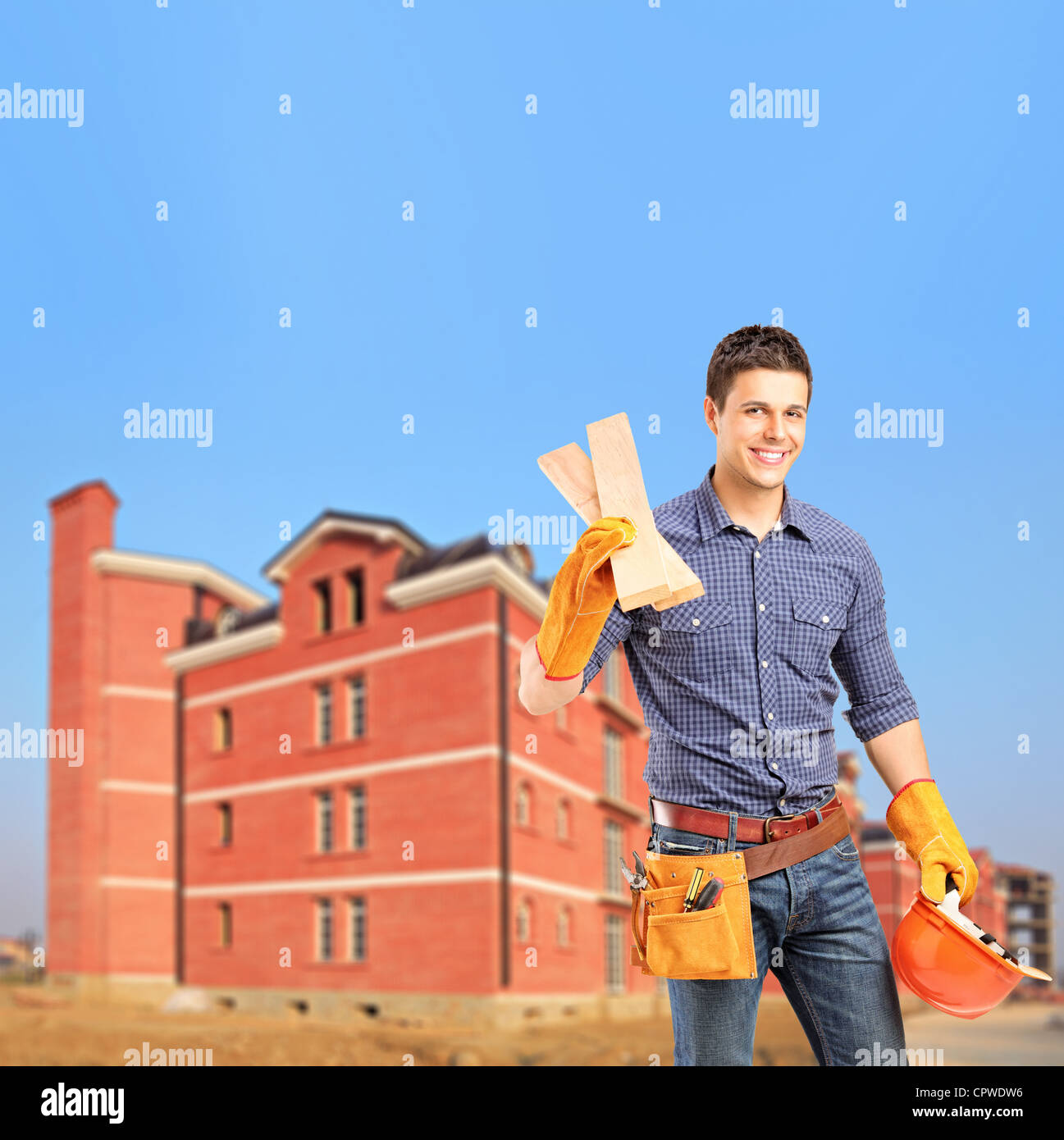 Smiling carpenter holding sills with a newly built apartment block in the background - Stock Image