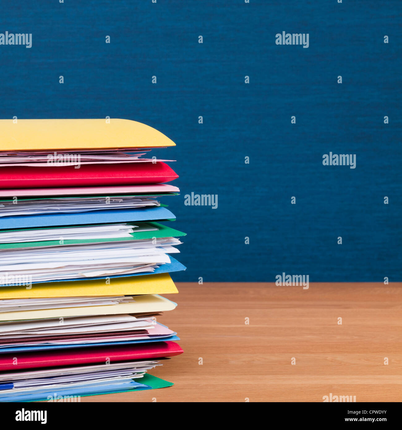 Tall stack of files full of paperwork, on a wooden surface with a blue wall behind. Copy space. - Stock Image