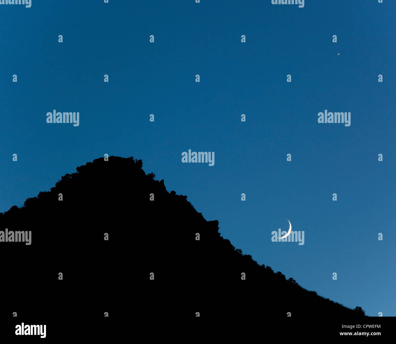 Silhouetted hill and blue twilight sky with evening star - Venus, and the setting crescent moon, Oregon - Stock Image