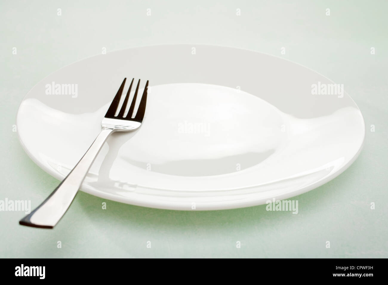 White plate and modern fork on simple plain green background. - Stock Image