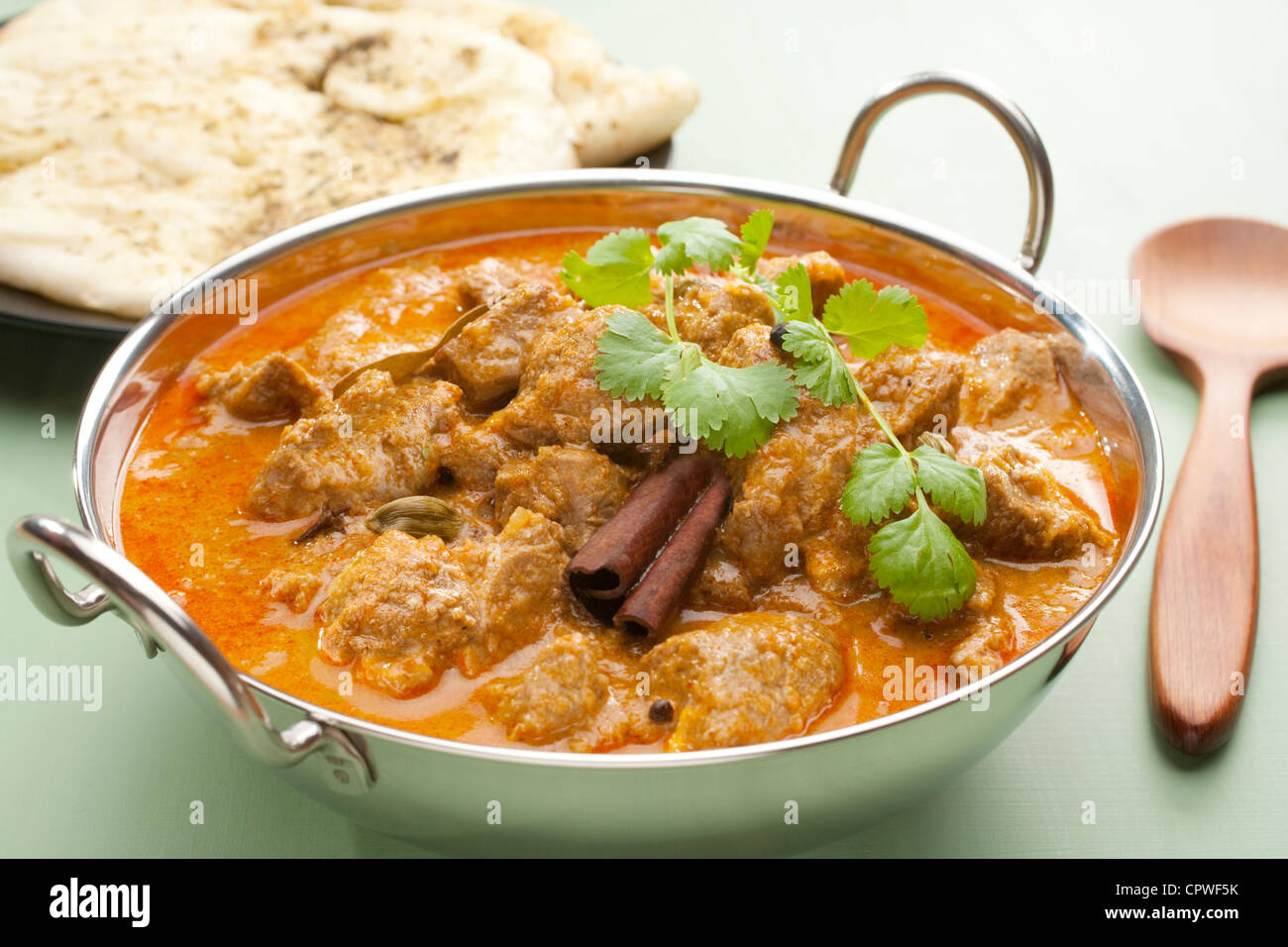 Indian curry lamb rogan josh in a steel karahi, with naan bread. - Stock Image