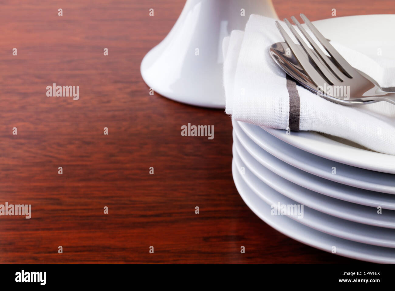Stack of small or dessert plates on a dark oak surface, cake stand in background. - Stock Image