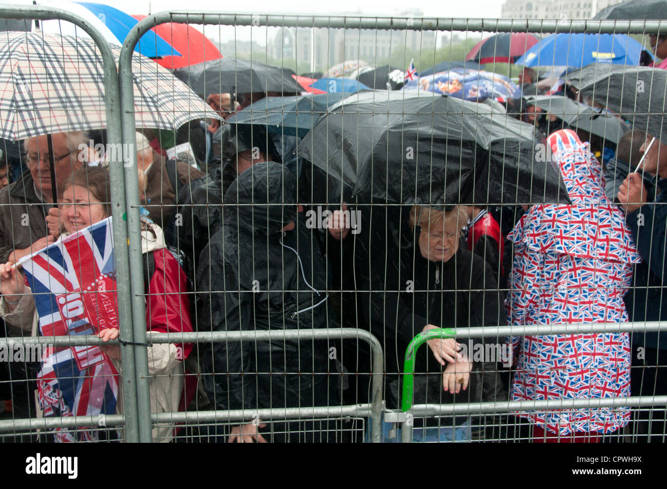 Queen Elizabeth Diamond Jubilee celebrations. Spectators watching the flotilla behind wire fence in pouring rain - Stock Image