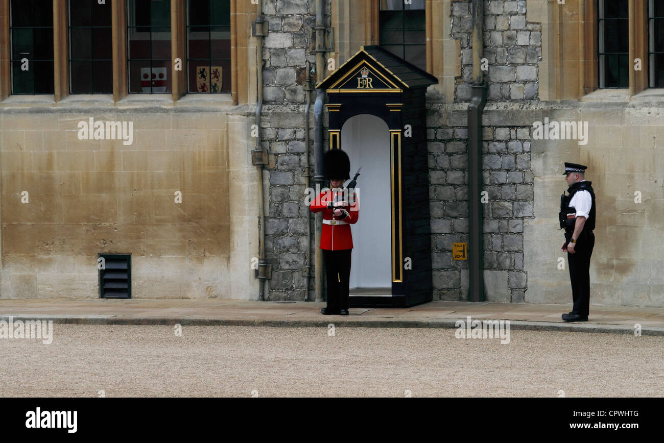 Windsor castle - The Upper Ward State Apartments - Coldstream Guardsman on guard duty watched by an armed policeman - Stock Image