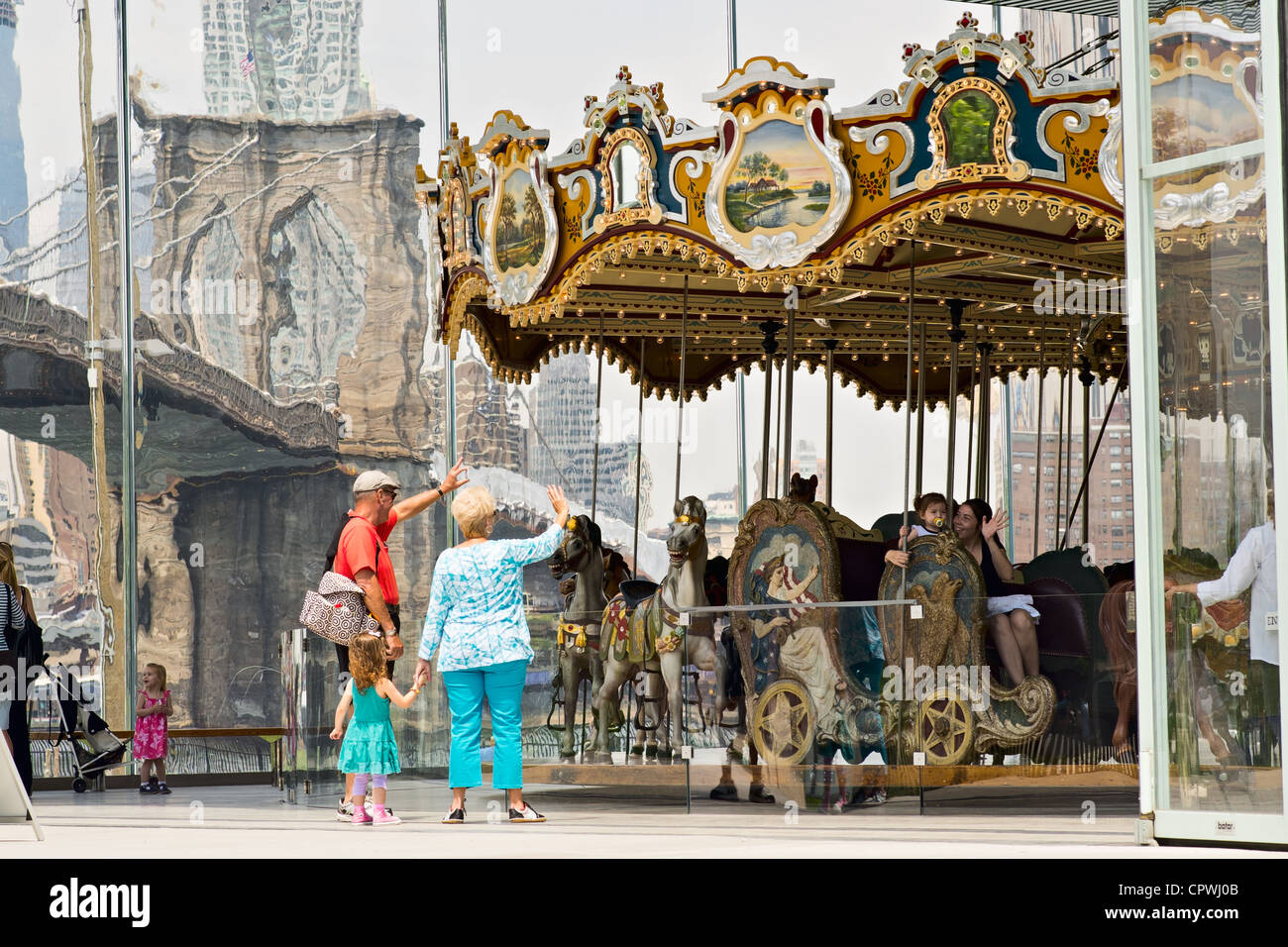 Older couple with young child wave at people on Jane's Carousel, Brooklyn Bridge Park, Brooklyn, NY, US - Stock Image