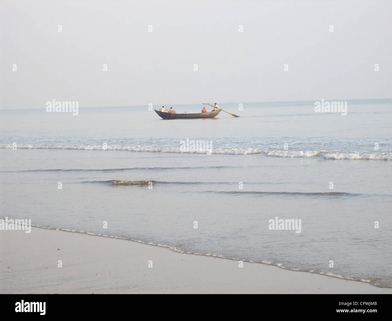 Boatmen moving their paddles to come at land during high tide. - Stock Image