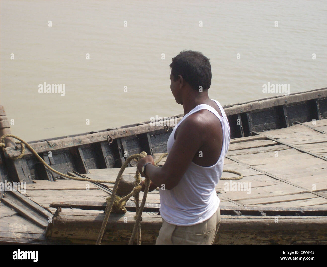 Boatmen tying their boat's rope with a log after returning from fishing. - Stock Image