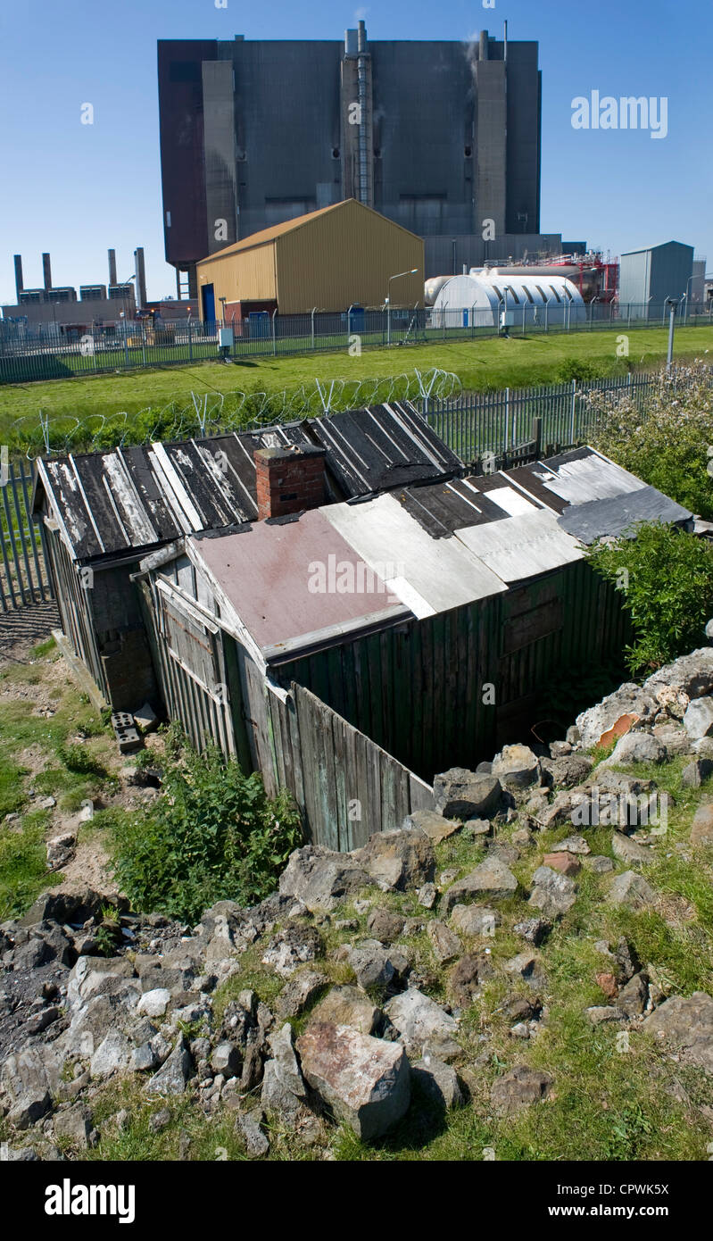 Wooden fishermens' shacks at the perimeter fence of Hartlepool nuclear power station. - Stock Image