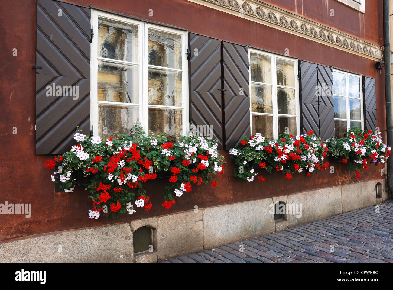 windows of antique house decorated with flowers - Stock Image