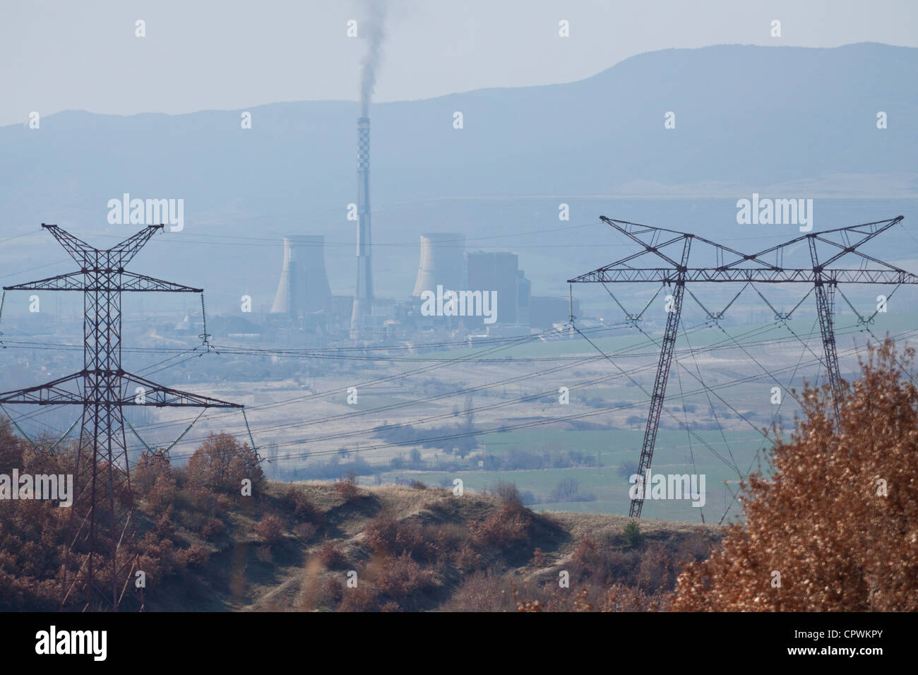 The Bobov Dol power plant producing a column of black smoke, seen between to electric pylons from a hill nearby - Stock Image