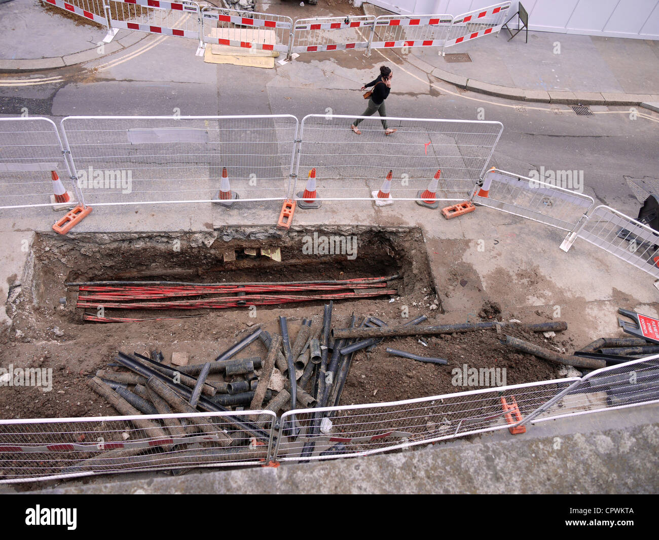 Road works, huge hole in road with cabling - Stock Image