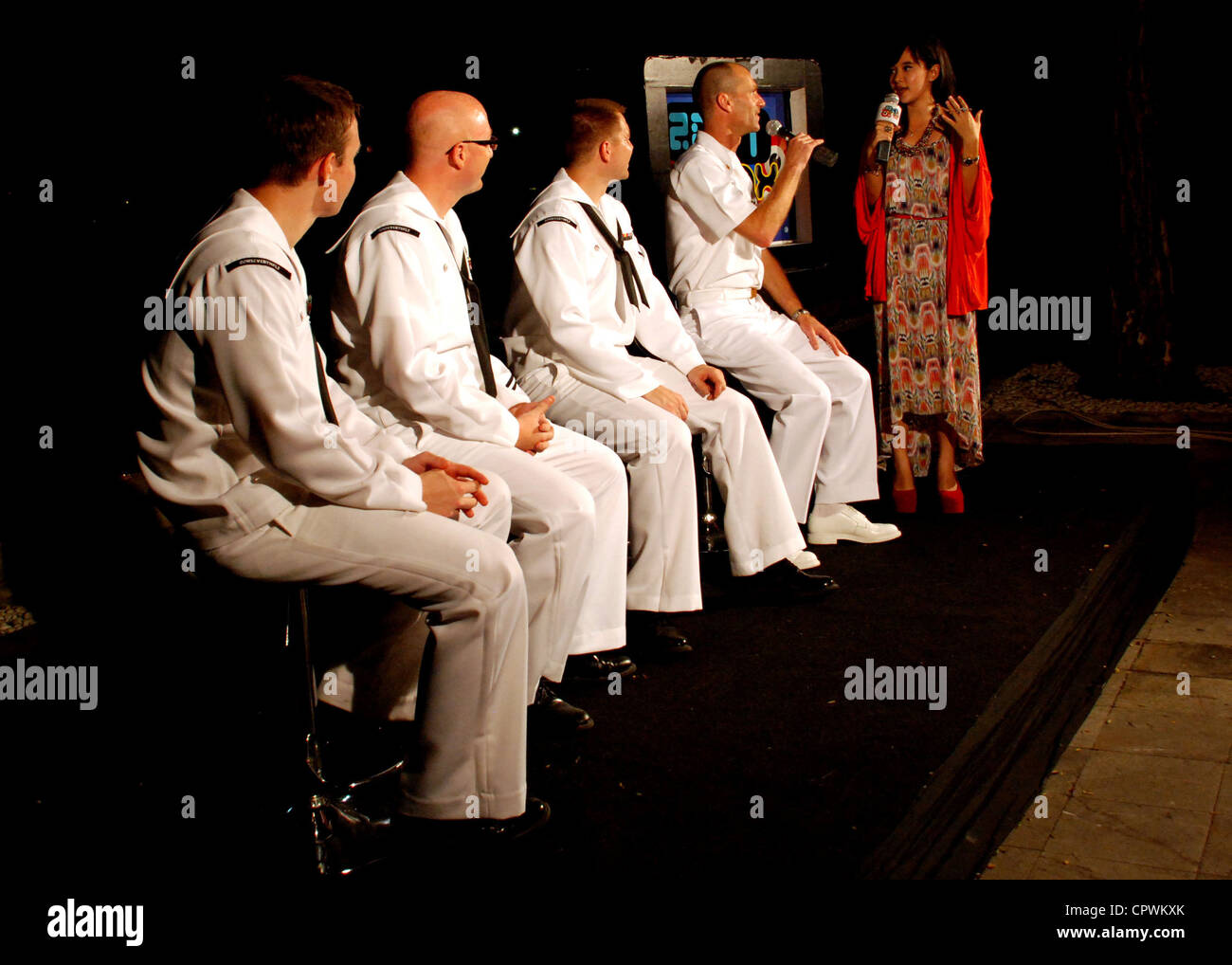 Members of the U.S. Navy 7th Fleet Band, Orient Express, conduct an interview with a J-Trax reporter, a local television Stock Photo