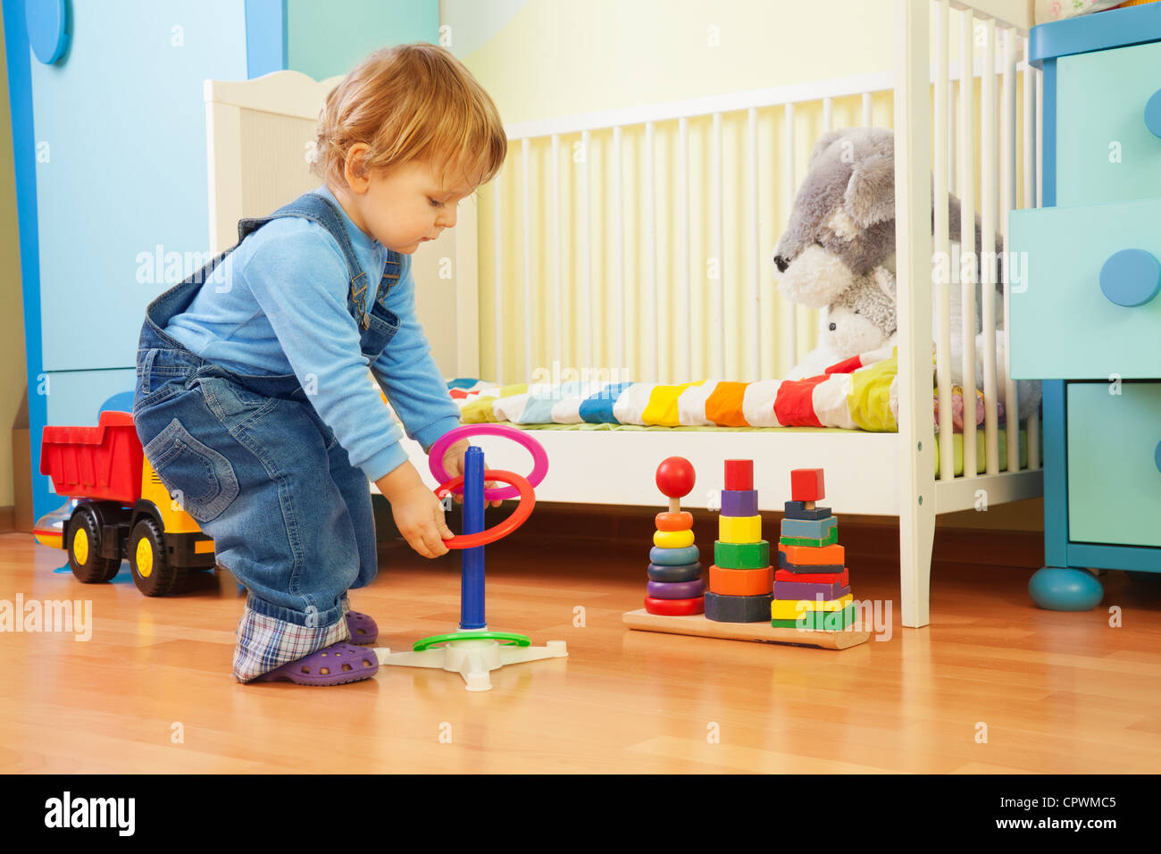 Boy playing with stacking rings in nursery room - Stock Image
