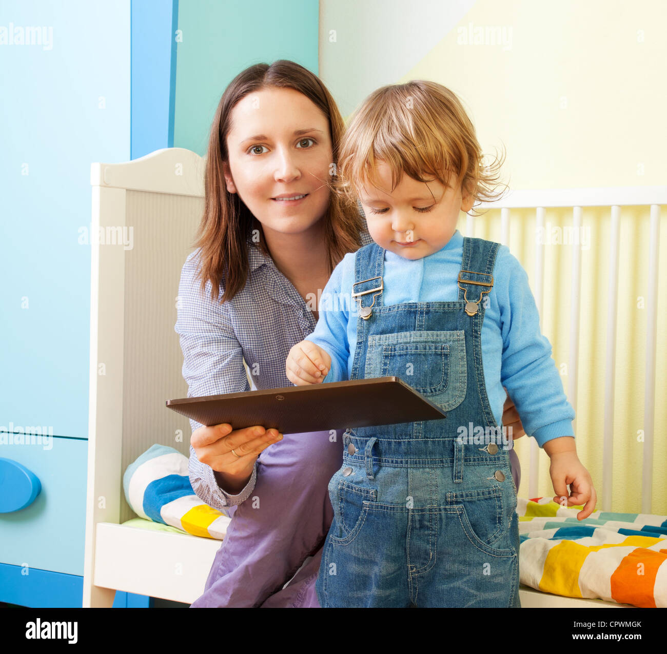 Happy mother with kid and tablet computer in nursery room - Stock Image