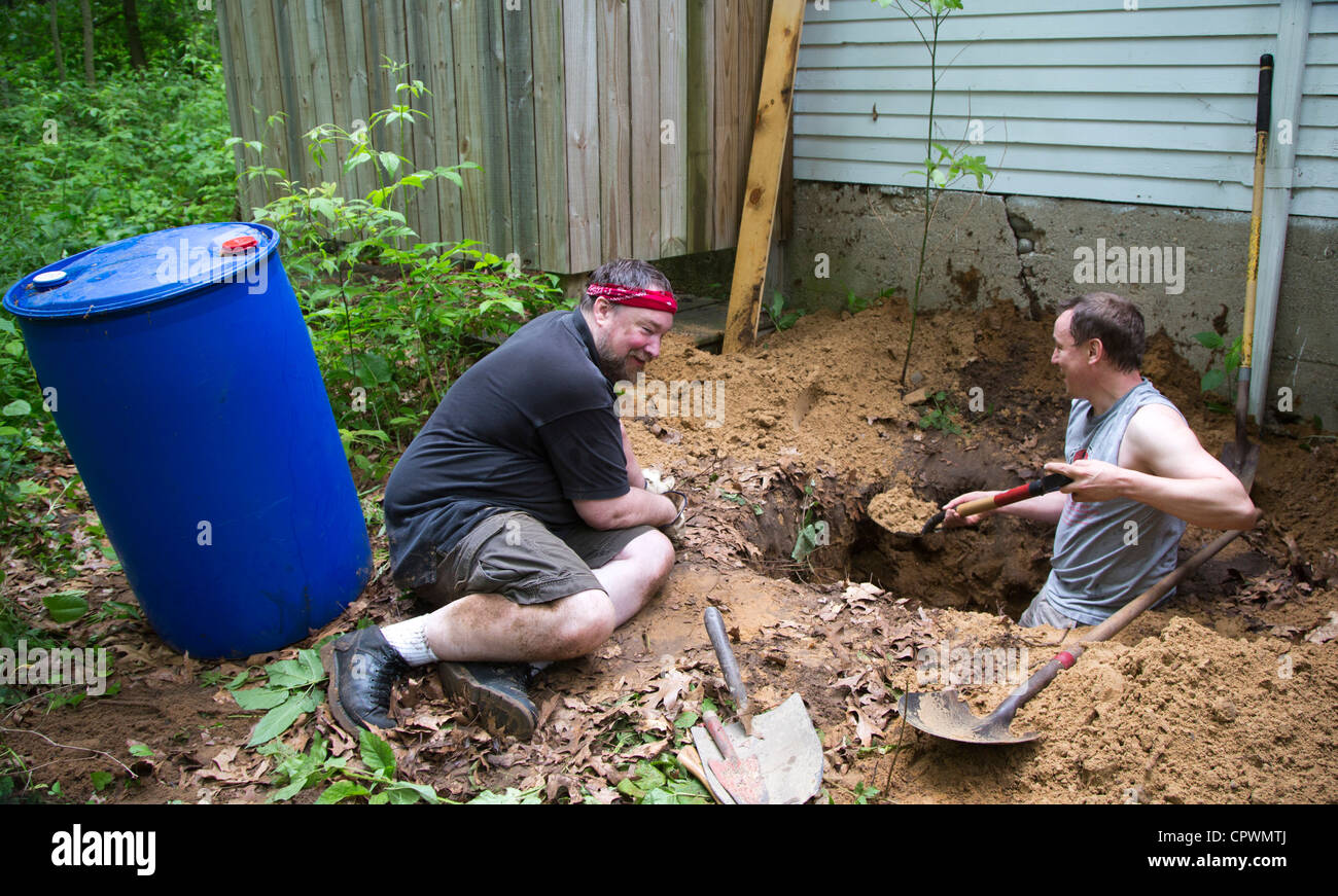 Men dig a hole to install a dry well at a summer cottage that lacks most plumbing. - Stock Image