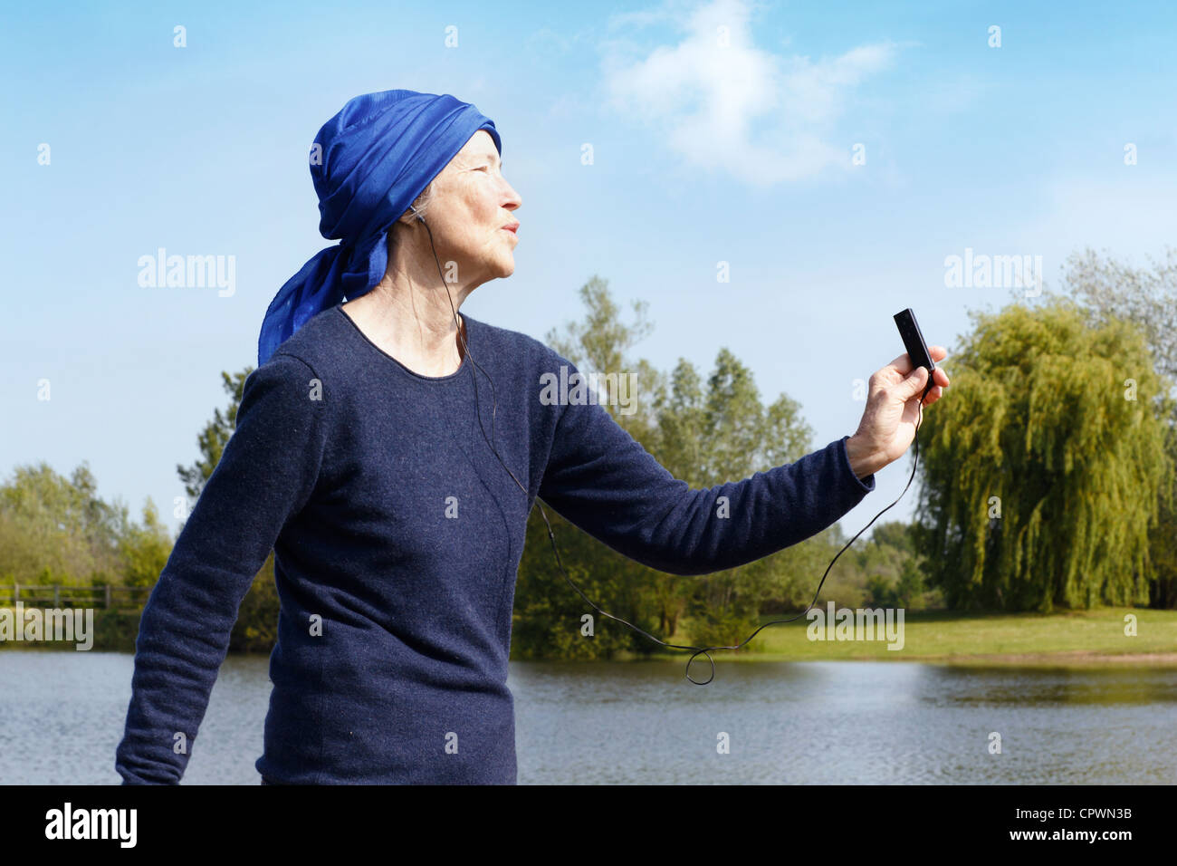 Senior woman with mp3 player by lake, side view. - Stock Image