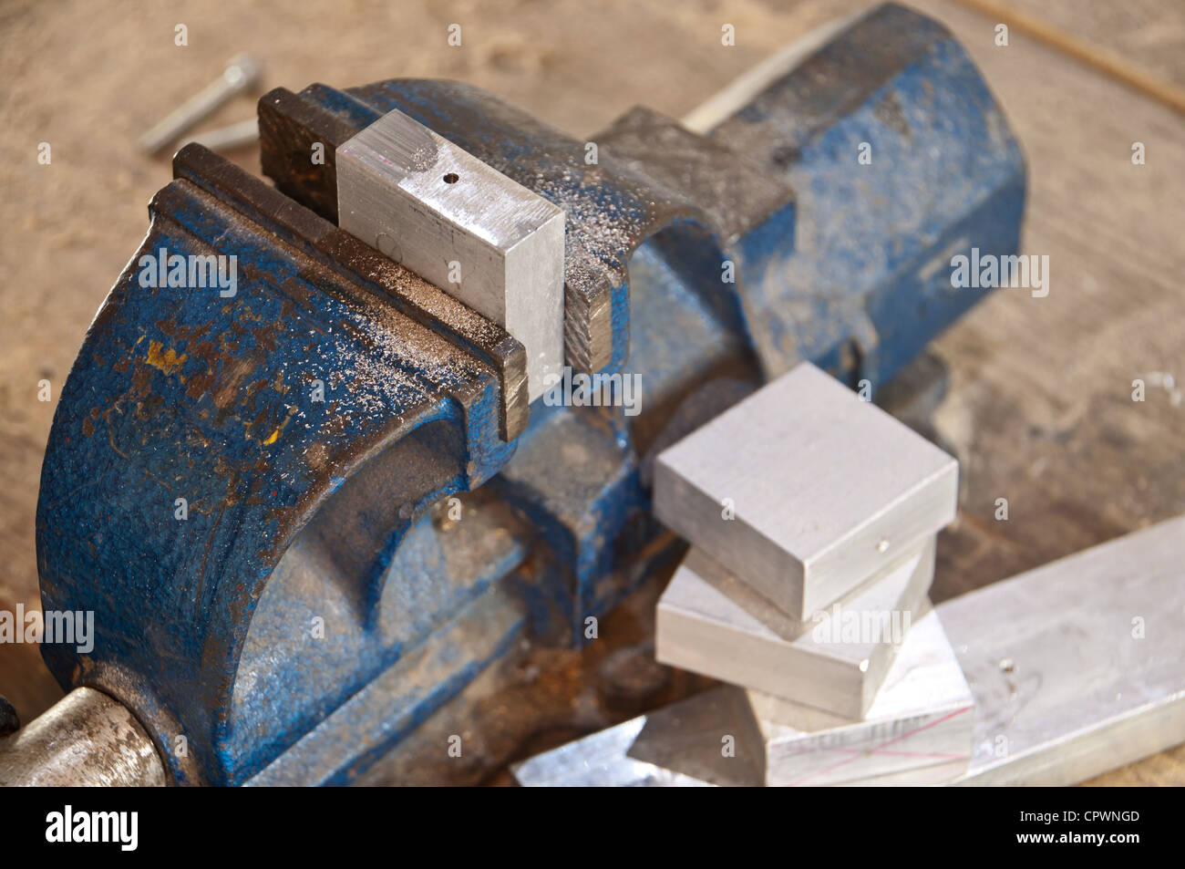Vice with a block of metal on a wooden workbench Stock Photo