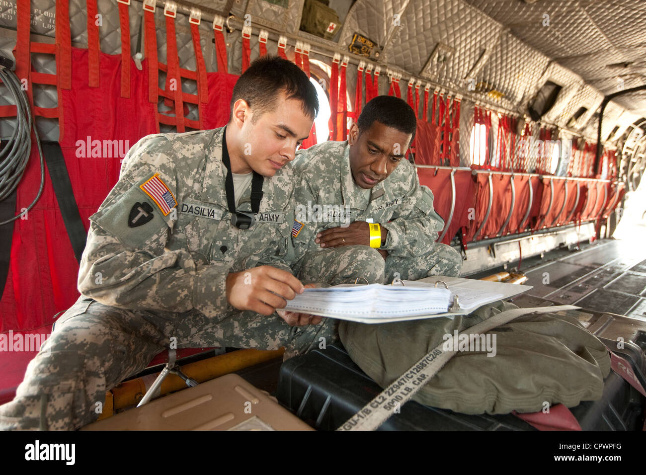 members of the United States Army in uniform review information inside a military aircraft for emergency disaster - Stock Image