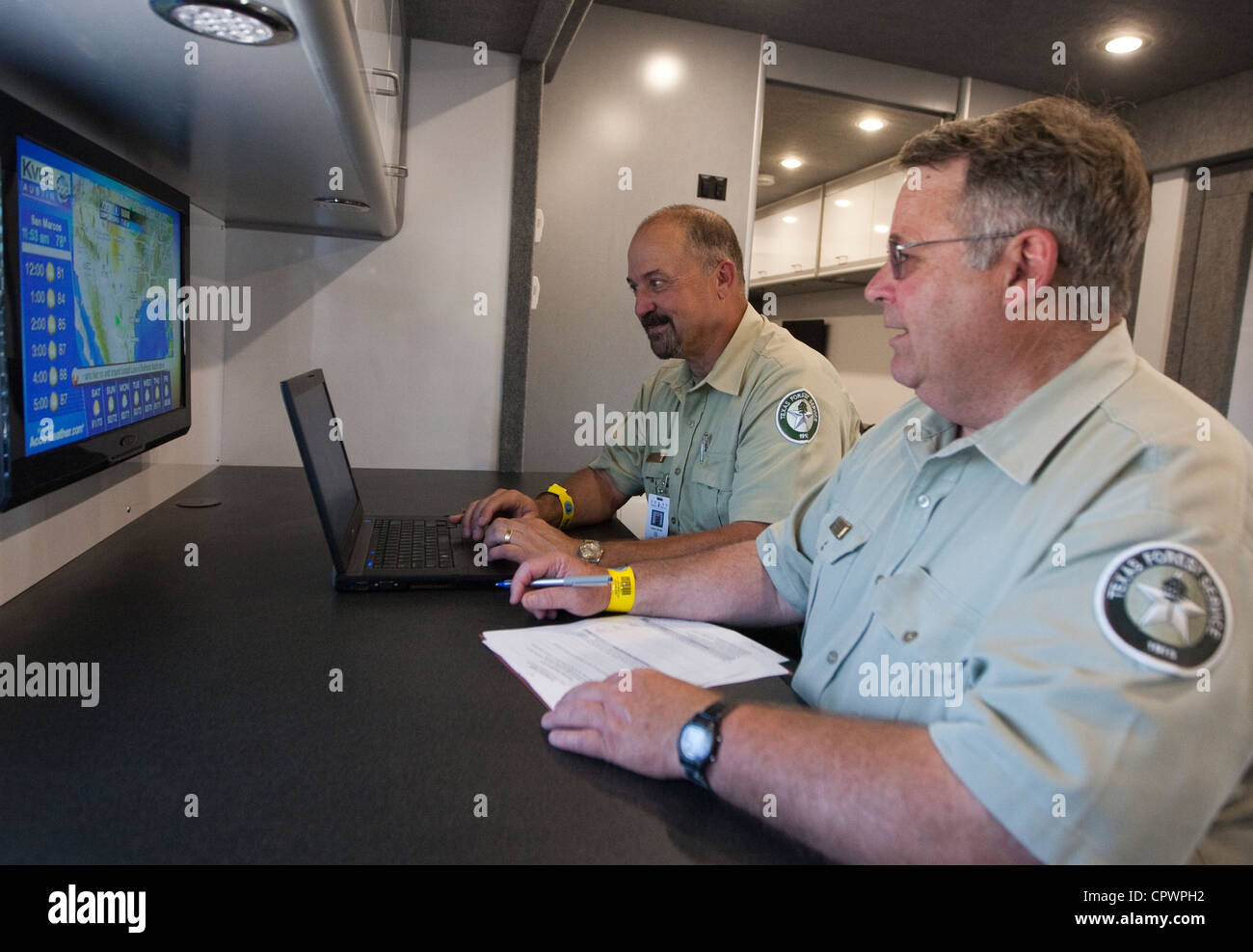 white male Texas Forest Service members review weather forecast on tv screen during a hurricane preparedness training - Stock Image