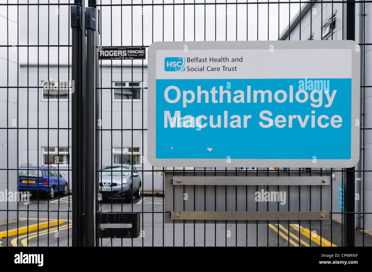Sign for 'Opthalmology Macular Service' outside a gate into a hospital. - Stock Image