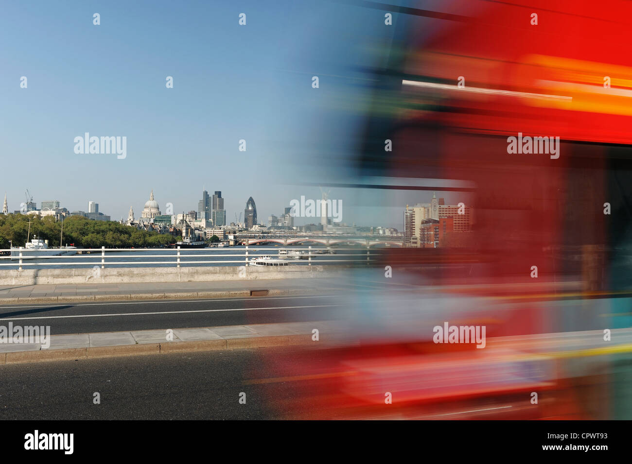Traffic speeds along Waterloo bridge with the City of London skyline behind - Stock Image