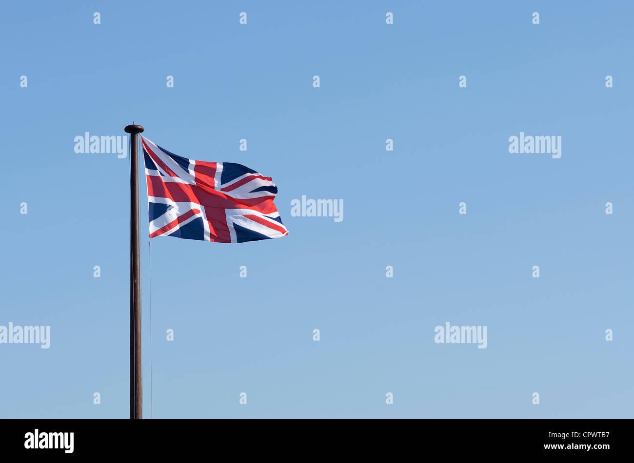 Union Jack flag flying against a blue sky - Stock Image