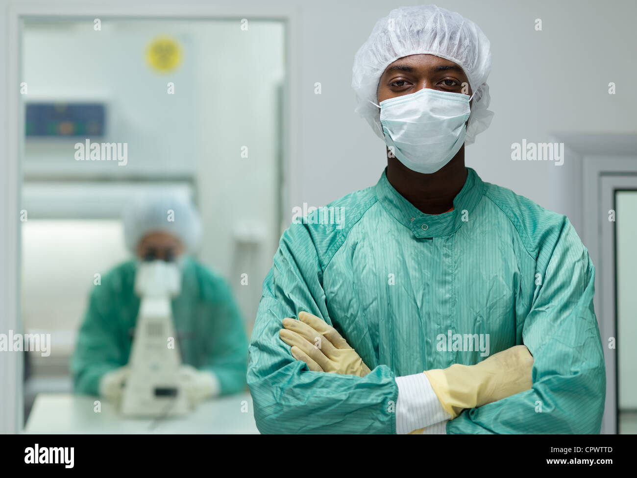 Portrait of man working in biotechnology research center with woman looking through microscope in background - Stock Image