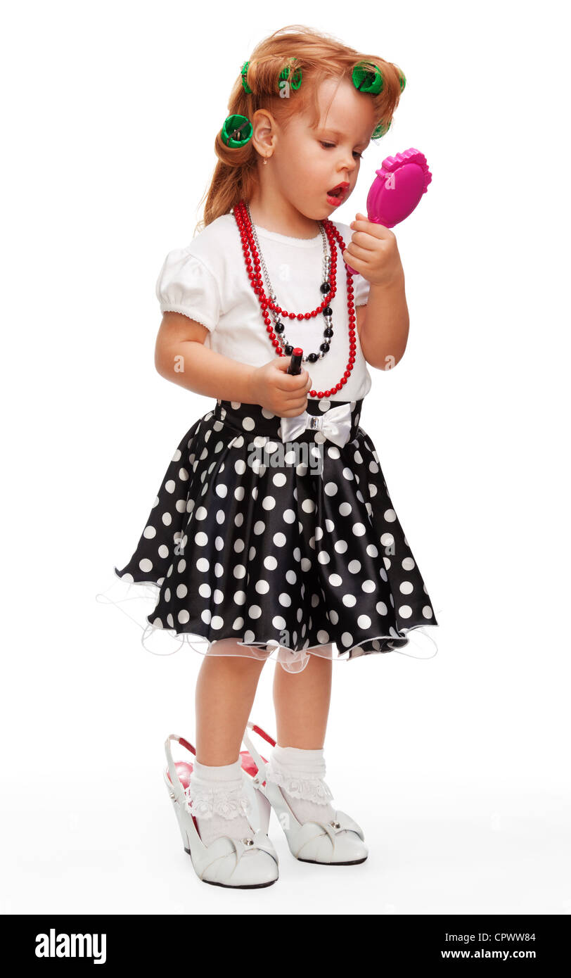 Little girl making up her face with lipstick, playing with mothers things - Stock Image