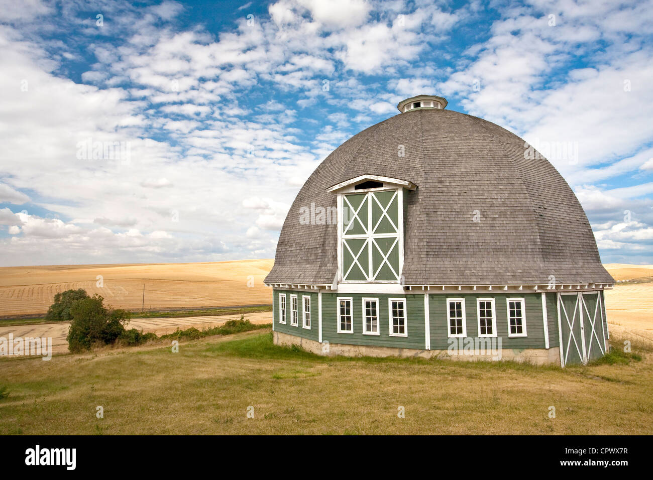 A scenic view of a round barn with a blue sky in the background. Stock Photo