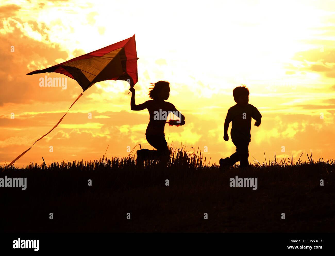 Two kids flying a kite at sunset invoke childhood memories. - Stock Image