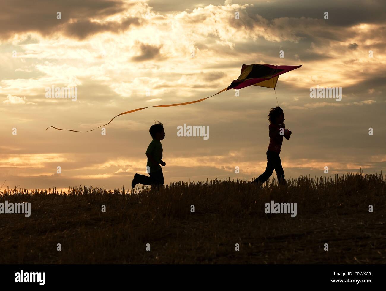 Two children enjoy flying a kite during sunset. - Stock Image