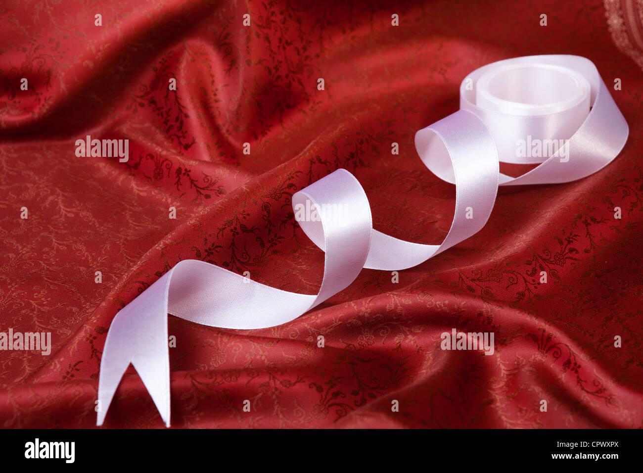 White ribbon on red drape silk fabric - Stock Image