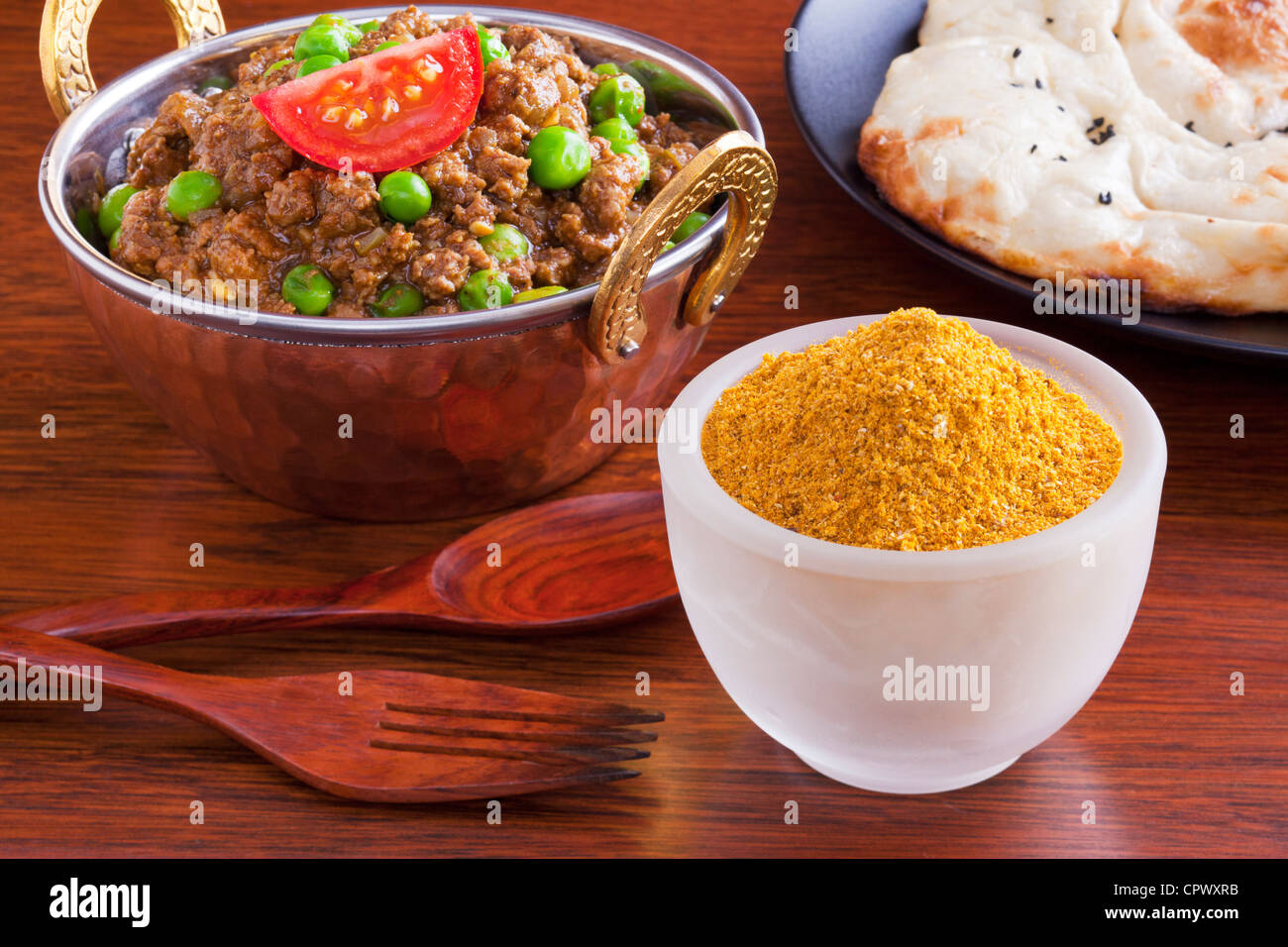 Curry powder with a beef mince curry, keema matar with peas, and naan bread. - Stock Image