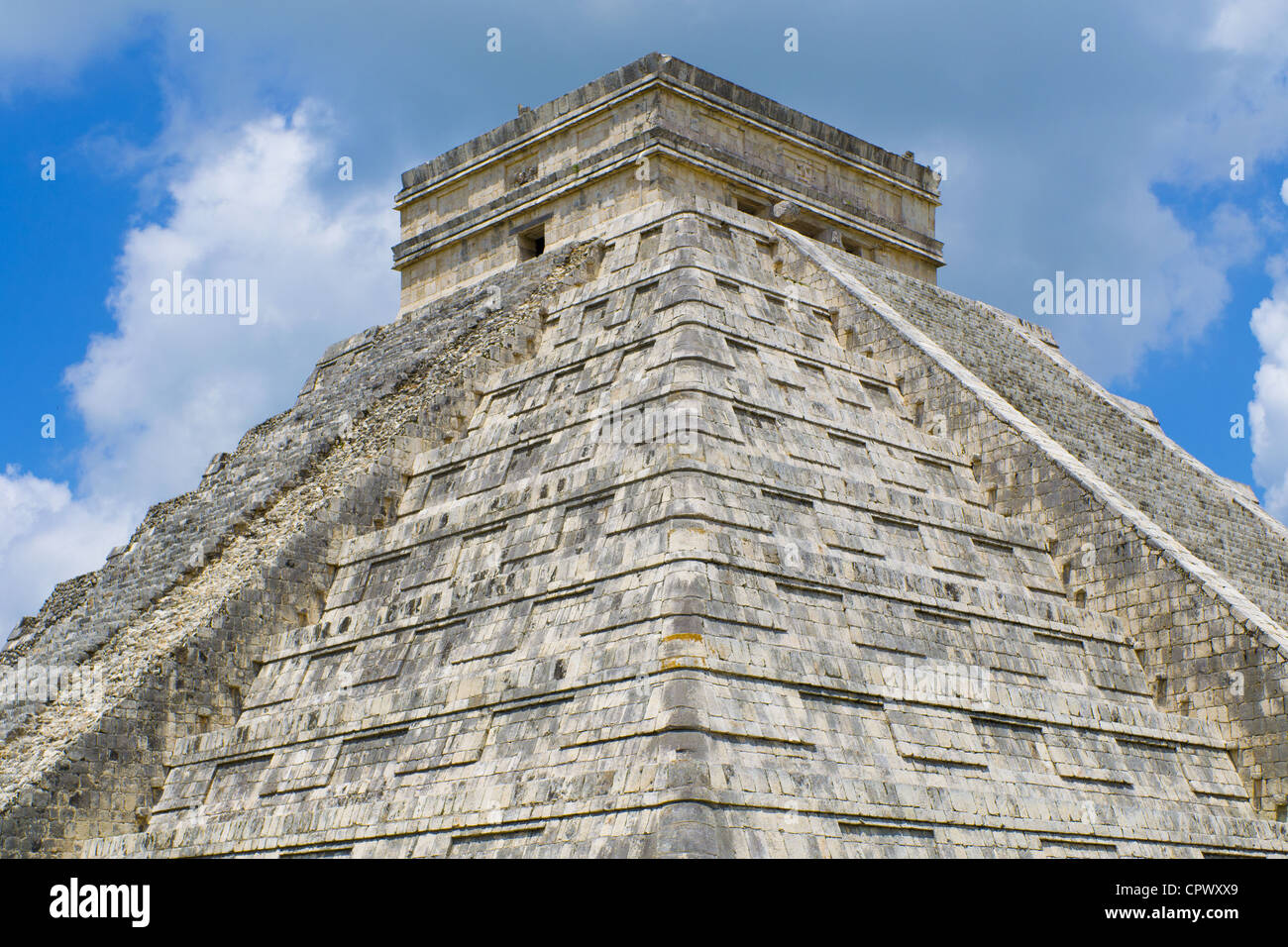 White puffy clouds over Mayan Pyramid of Kukulkan (also known as El Castillo) and ruins at Chichen Itza Yucatan - Stock Image