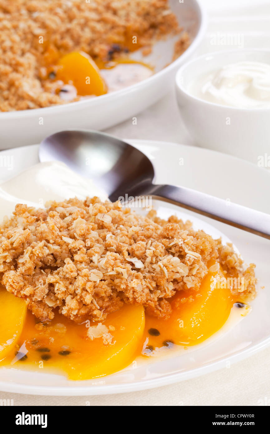 An unusual fruit crumble with peach and passion fruit. The crumble contains wholemeal flour, brown sugar and oats. - Stock Image